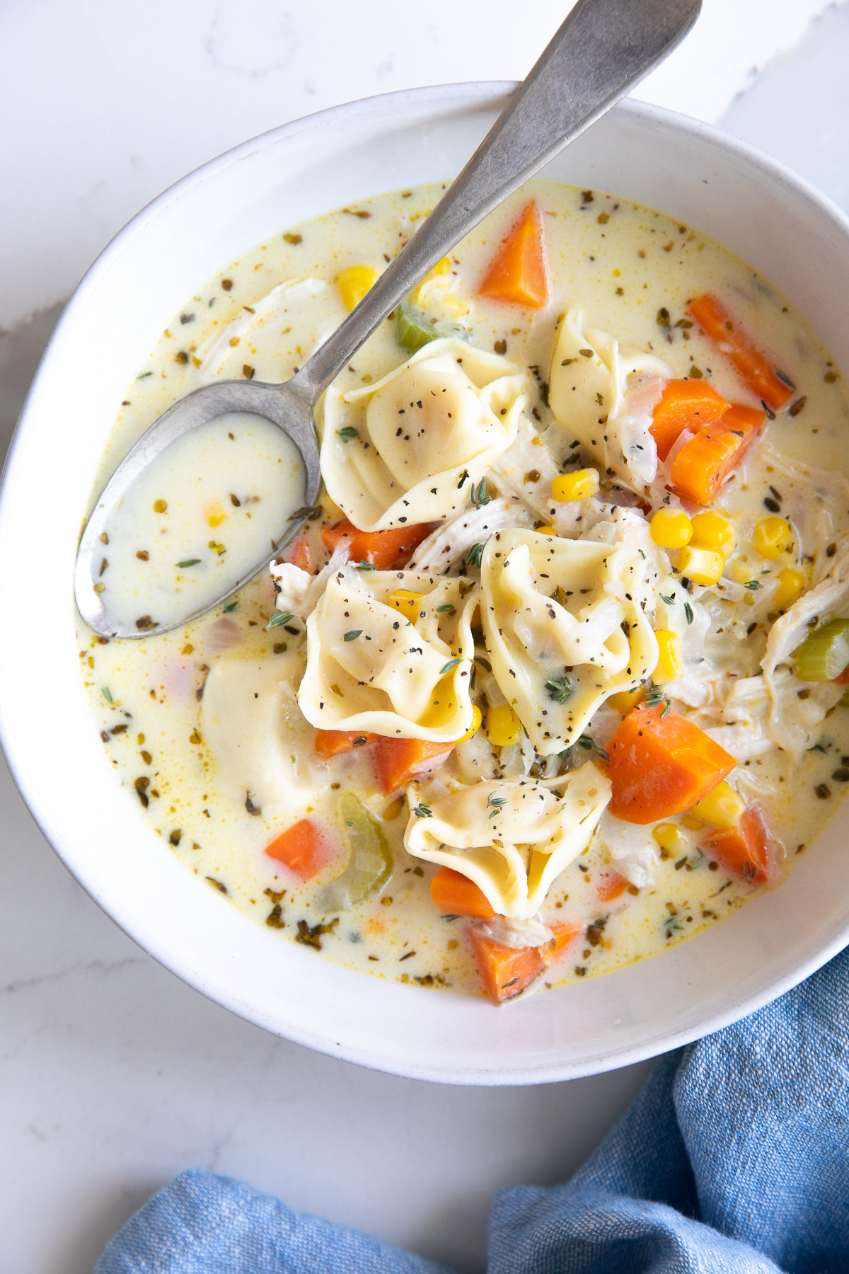 Image of a white bowl with a blue napkin filled with creamy chicken tortellini soup and garnished with fresh thyme.