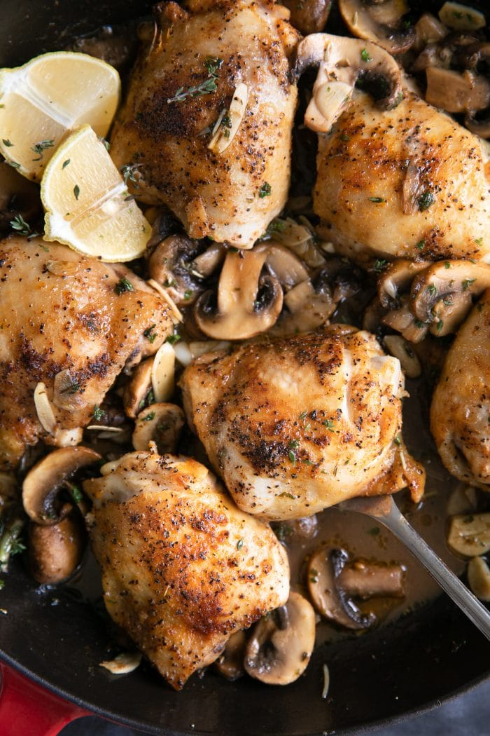 Overhead image of cooked chicken thighs in a light mushroom garlic sauce in a large skillet.