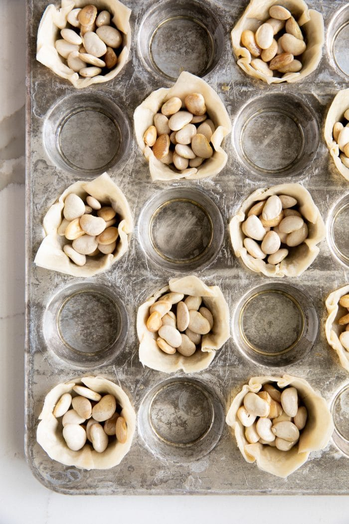 Image of homemade phyllo cups before being baked in a mini muffin tin and filled with beans.