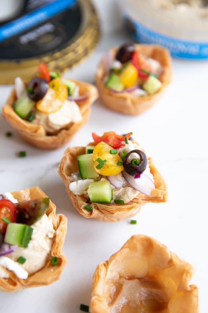 Image of mini phyllo cups filled with classic hummus and topped with chopped tomatoes, cucumber, sliced red onion, olives, and chives.