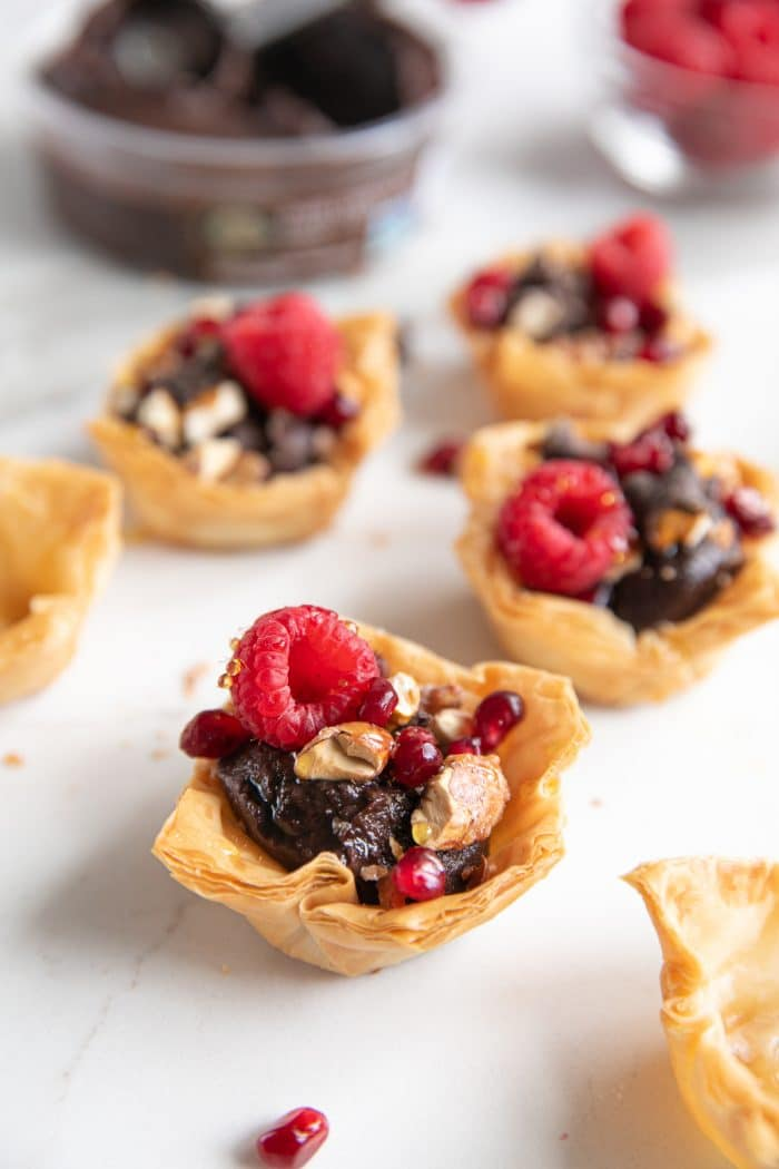 Image of mini phyllo cups filled with chocolate hummus and topped with crushed chocolate covered pretzels, candied almonds, pomegranates, and raspberries.
