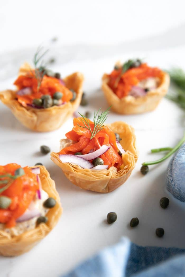 Image of four mini phyllo cups filled with everything bagel hummus and topped with thinly sliced onions, smoked salmon, capers, and fresh dill.