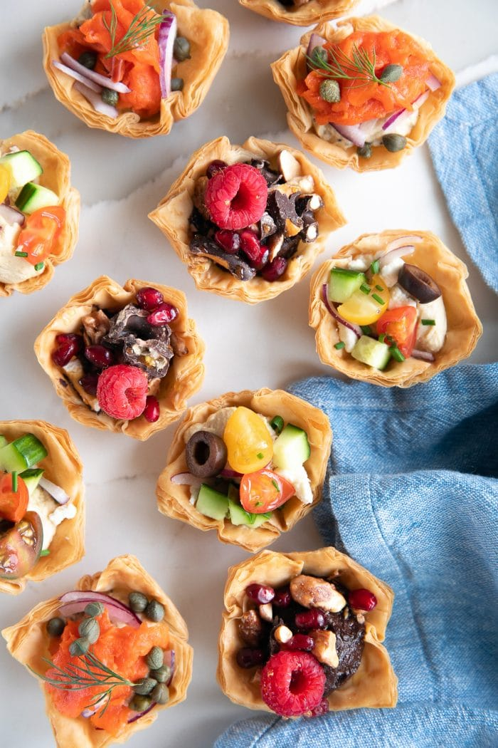 Image of Homemade phyllo cups filled with hummus and various toppings such as tomatoes, cucumbers, and feta cheese; chocolate covered pretzels, nuts, and berries; capers, sliced red onion, and smoked salmon.