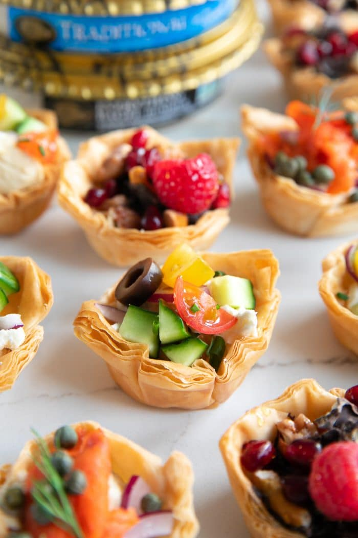 Homemade phyllo cups filled with hummus and various toppings such as tomatoes, cucumbers, and feta cheese; chocolate covered pretzels, nuts, and berries; capers, sliced red onion, and smoked salmon.