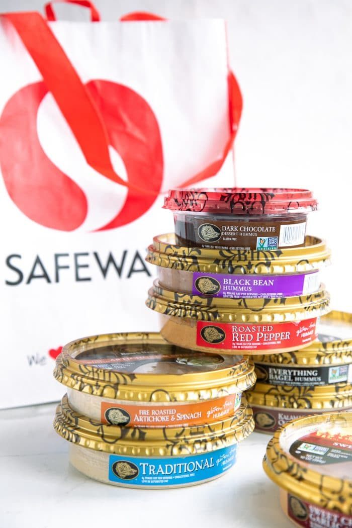 Image of small stacks of Boar's Head hummus stacked on top of each other with a Safeway shopping bag behind them.