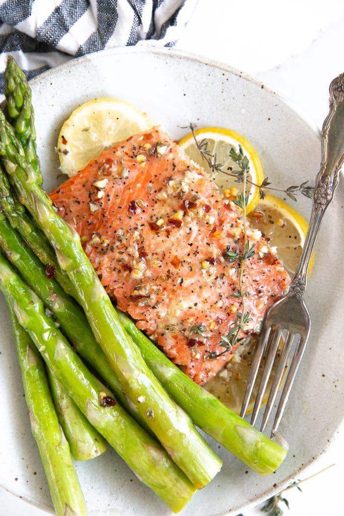 Small dinner plate with a serving baked salmon with lemon butter and steamed asparagus.