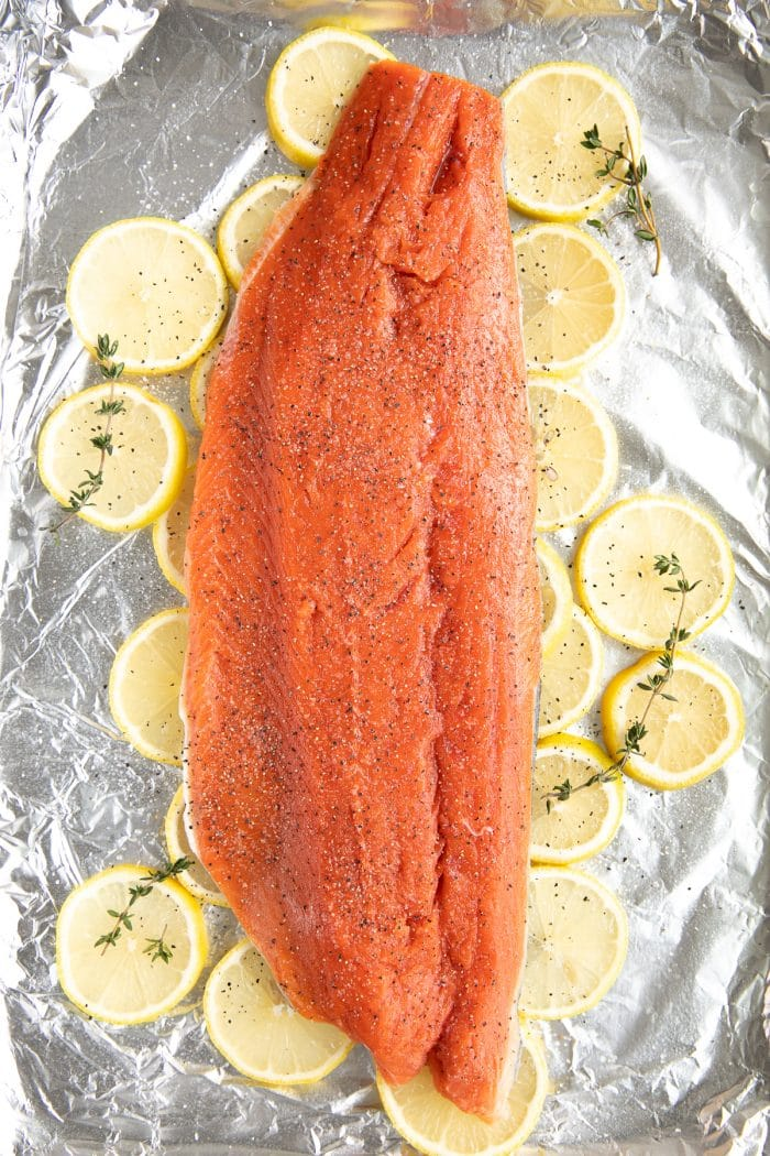 Image of a baking sheet lined with foil, topped with sliced lemons, and topped with a large wild salmon fillet garnished with fresh thyme.