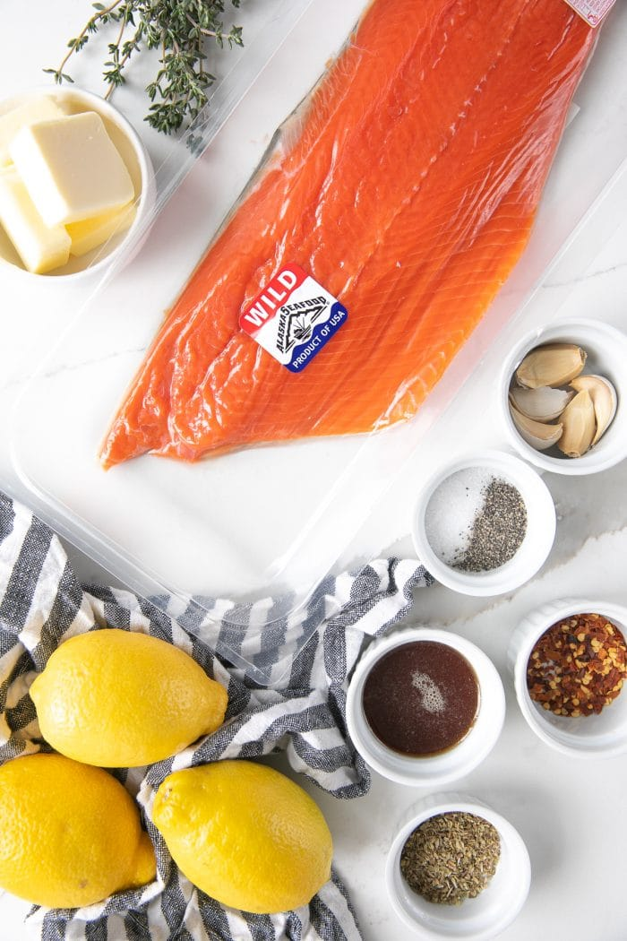 Ingredients needed to make easy baked salmon including butter, wild salmon, garlic cloves, red chili flakes, salt, pepper, honey, Italian seasoning, and lemons.
