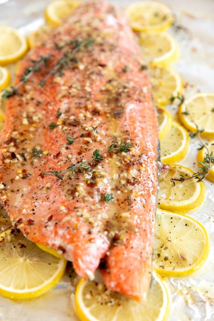 Close up image of baked salmon covered in a lemon butter sauce and garnished with fresh thyme.