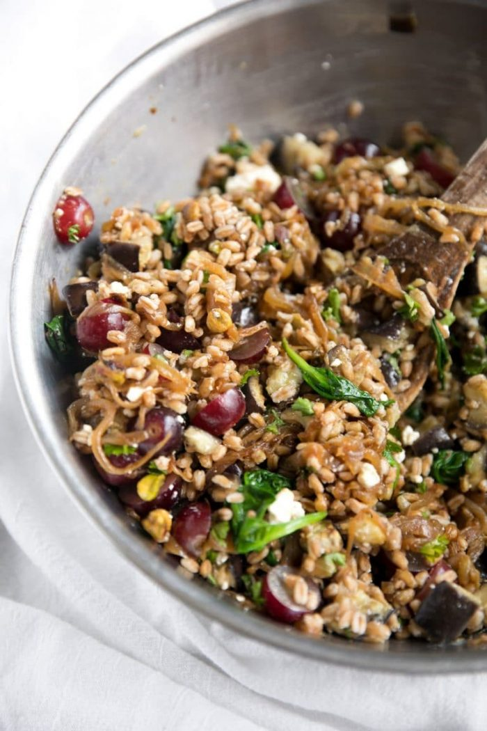 Image of a large mixing bowl filled with a farro salad made up of sliced grapes, spinach, feta cheese, pistachios, caramelized onions, and roasted eggplant.
