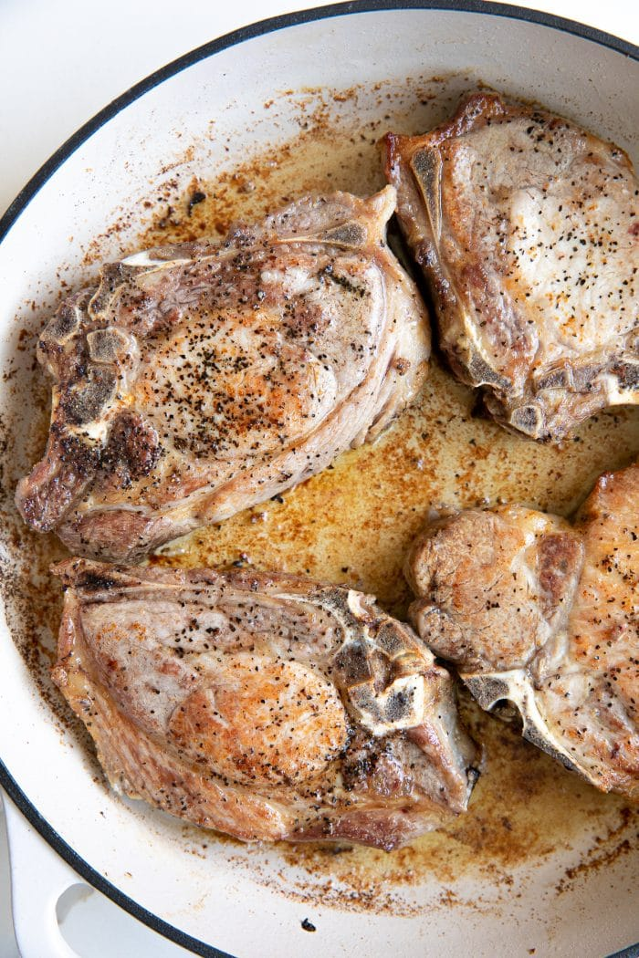 Image of a white ceramic skillet filled with seared bone-in pork chops.