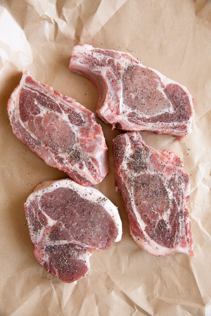 Image of four raw bone-in pork chops on broth butcher paper.