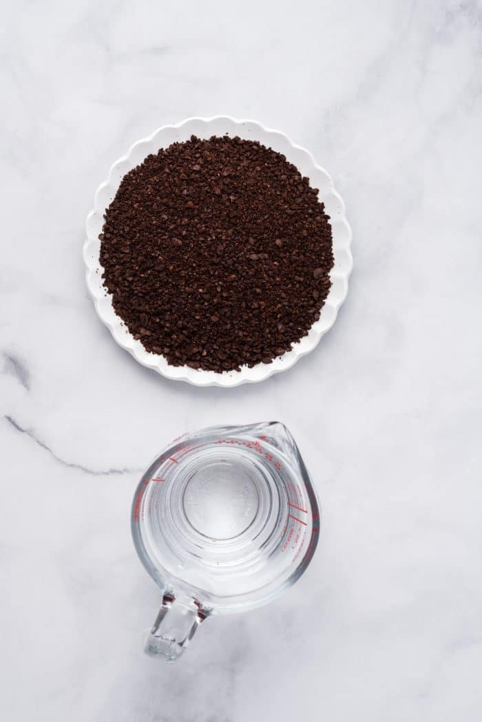 Overhead image of coffee grounds and a measuring cup filled with water.
