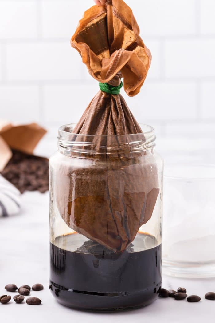 Image of cold brew coffee straining into a large glass jar.