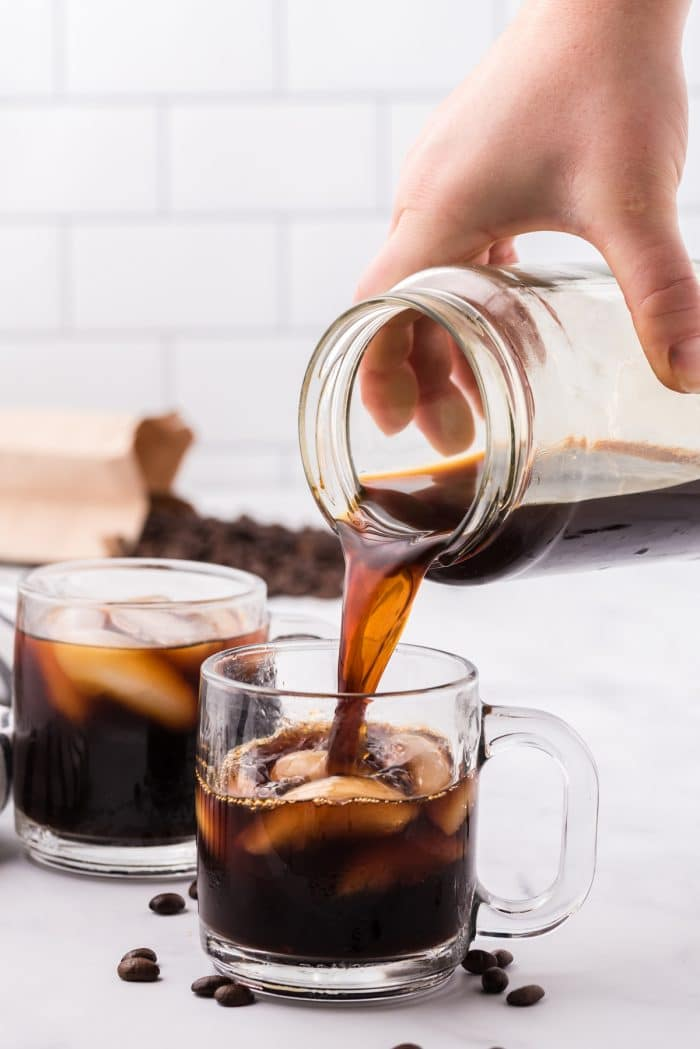 Image showing cold brew coffee being poured into a glass mug filled with ice.