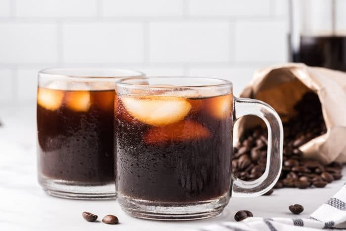 Image of two mugs filled with iced coffee and ice.