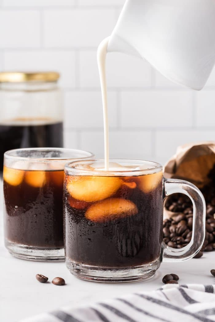 Image showing milk being poured into a glass coffee mug filled with iced cold brew coffee.