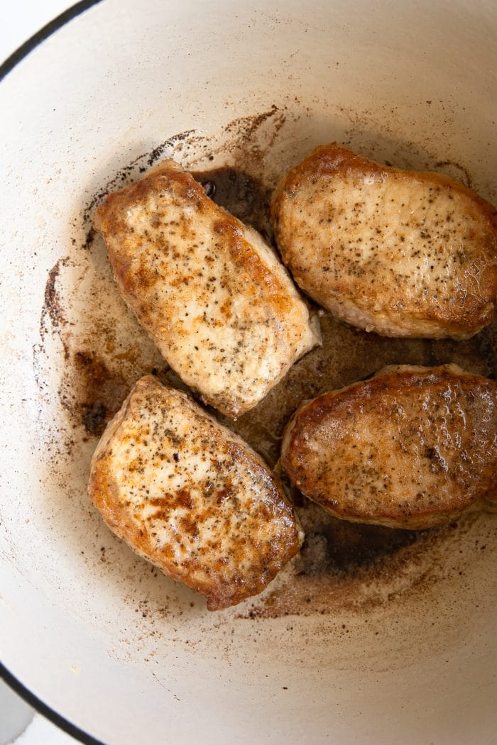 Image of four seared pork chops in a large Dutch oven.