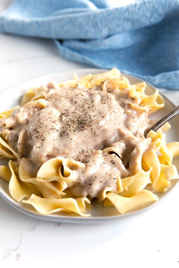 Plate filled with egg noodles covered in cream of mushroom soup sauce and a single boneless pork chop.