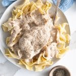 Overhead image of a plate filled with egg noodles and topped with a large pork chop with mushroom gravy.