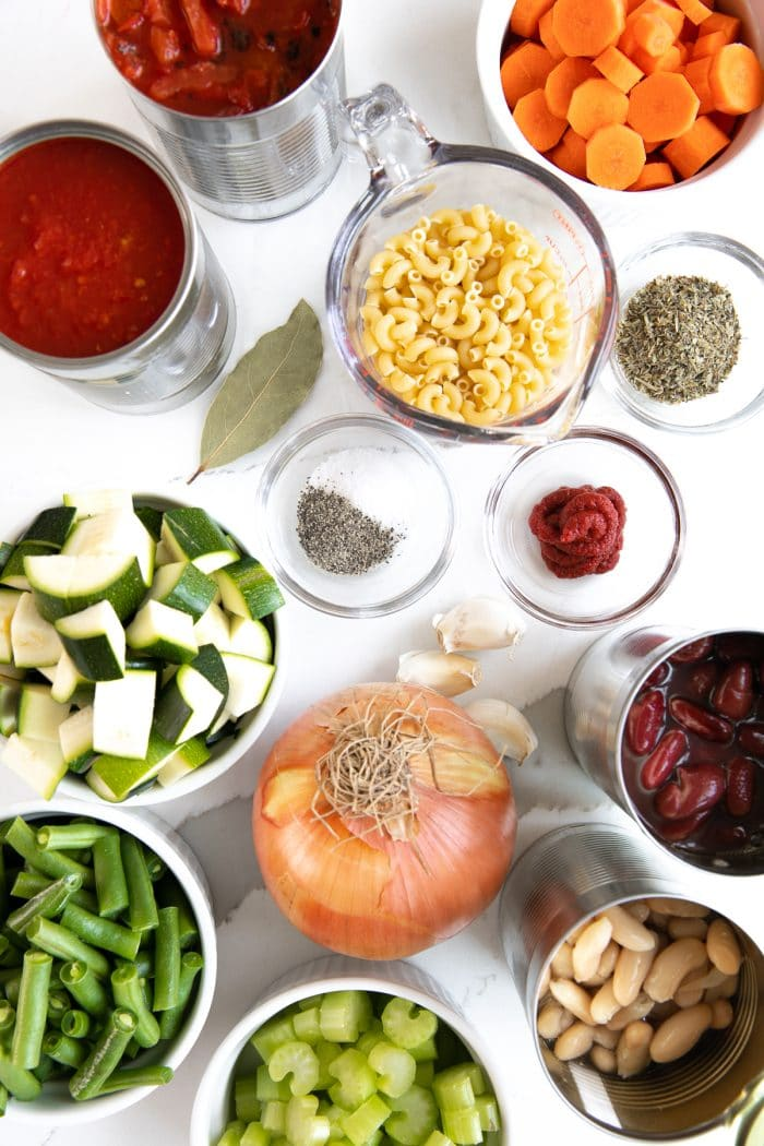 Ingredients needed to make minestrone soup including canned tomatoes, pasta noodles, canned beans, chopped vegetables, and dried herbs.