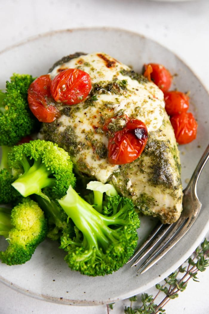 Small dinner plate with one chicken breast covered in pesto and melted mozzarella cheese and served with burst cherry tomatoes and steamed broccoli.