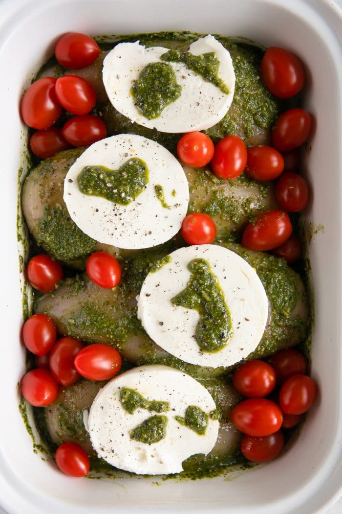 White baking dish filled with four raw chicken breasts covered in pesto sauce and topped with a large round slice of fresh mozzarella cheese and fresh cherry tomatoes.