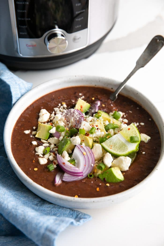 Large shallow soup bowl filled with Instant Pot black bean soup and topped with crumbled white cheese, avocado, red onion, red chili flakes, and fresh lime wedge.