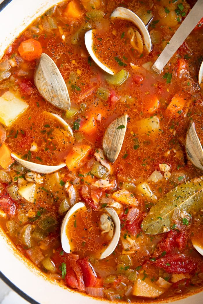 Overhead image of a large pot of Manhattan clam chowder filled with carrots, celery, onion, potatoes, little neck clams, all simmering in a tomato and clam broth.