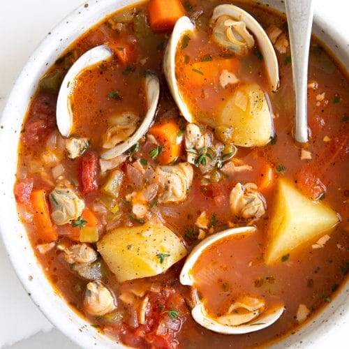 Overhead image of a white soup bowl filled with homemade Manhattan clam chowder recipe made with little neck clams, potatoes, carrots, in a light tomato clam broth.