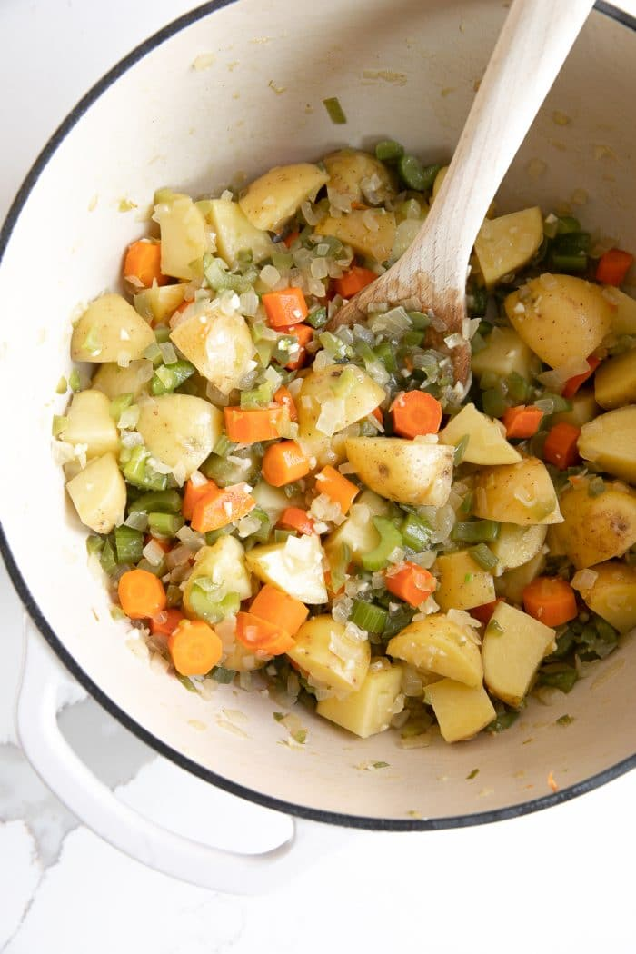 Image of a large white ceramic pot filled with cooking diced onion, carrots, celery, potatoes, and garlic.