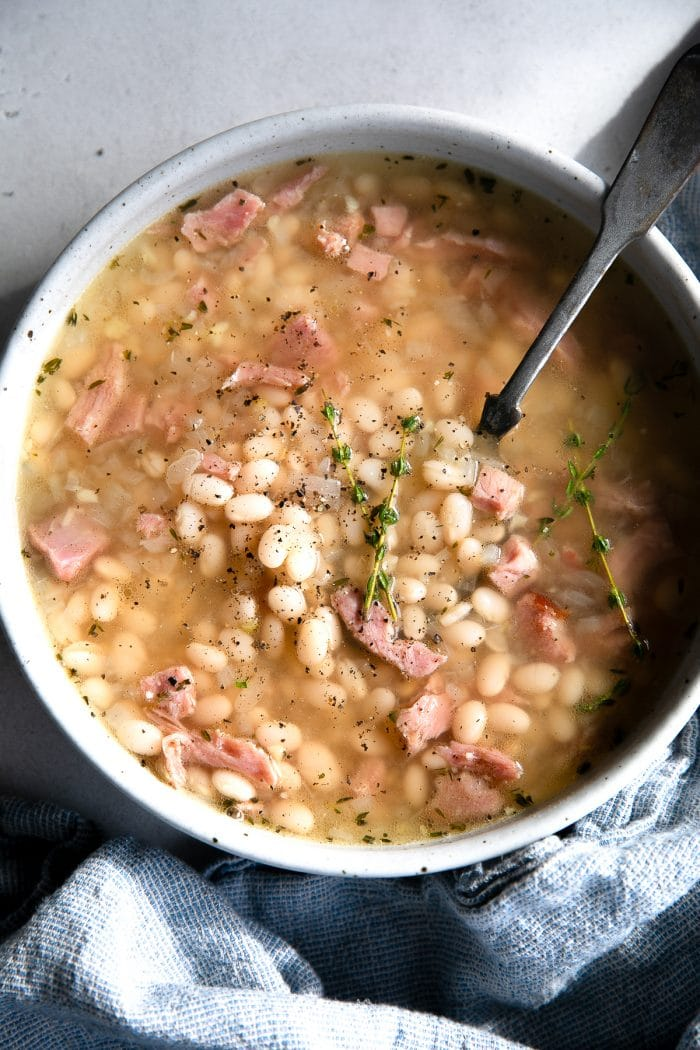 White soup bowl filled with navy bean soup made with chunks of leftover ham, cooked navy beans, and fresh thyme in a light broth.