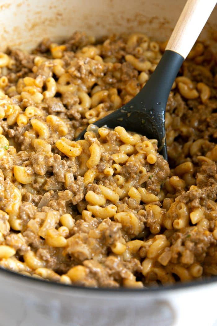 Large white ceramic Dutch oven filled with homemade hamburger helper made with ground beef and macaroni noodles.