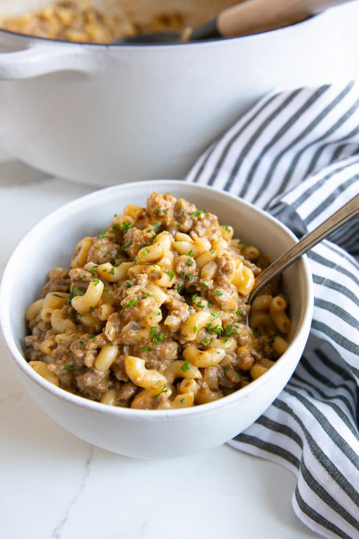 Image of a white bowl filled with homemade one-pot hamburger helper and garnished with minced parsley.