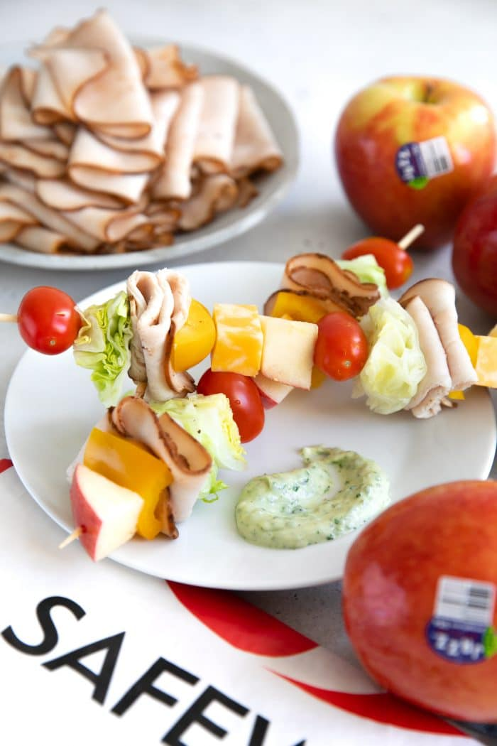 Small white plate with two deli salad skewers filled with tomatoes, cheese, lettuce, sliced turkey, bell pepper, and apples, with a spoonful of basil mayonnaise.
