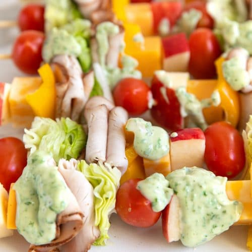Wooden skewers with repeating layers of cherry tomatoes, iceberg lettuce, sliced Boar's head turkey, cubes of cheese, bell pepper, and cubes of Jazz apples topped with globs of basil mayonnaise.