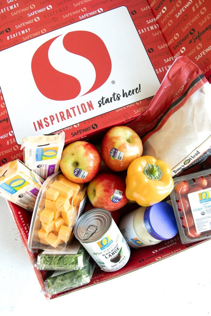 Overhead image of a red Safeway box with the following inside: Jazz apples, cubed cheddar cheese, jar of mayonnaise, fresh basil, Boar's Head sliced turkey, yellow bell pepper, black olives, and colby cheese.
