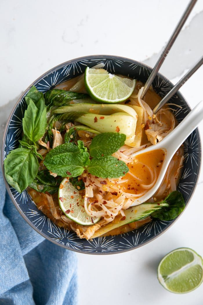 Image of a blue soup bowl filled with Thai chicken curry noodle soup made with a coconut curry broth, rice noodles, shredded chicken, and bok choy, and garnished with fresh mint, limes, and fish sauce.