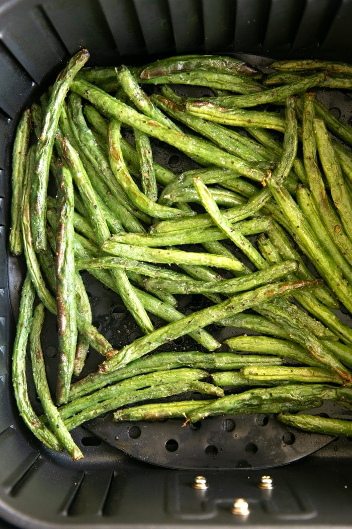 Fully roasted and cooked air fryer green beans still in the basket of a large air fryer.