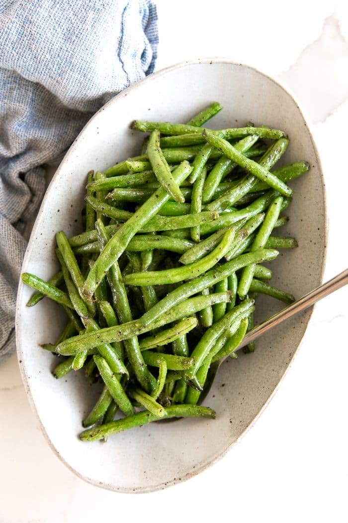 Oval serving plate filled with green beans that were cooked in an air fryer.