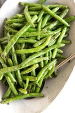 Oval serving dish filled with perfectly cooked air fryer green beans.