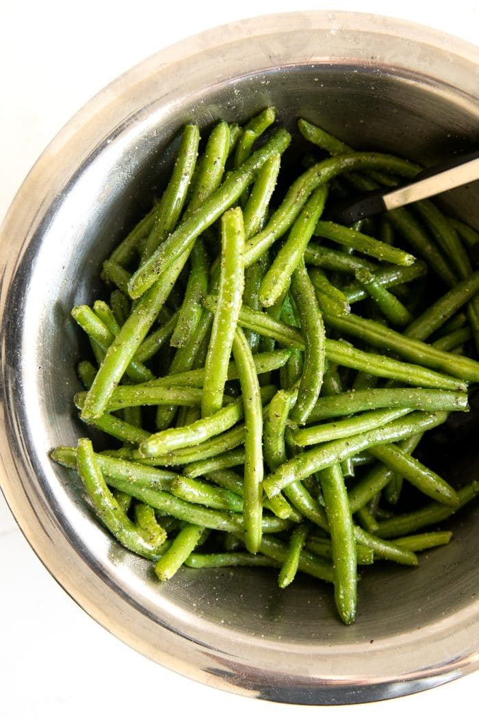 Large mixing bowl filled with green beans that have been tossed in olive oil and seasoned with salt, pepper, and garlic powder.