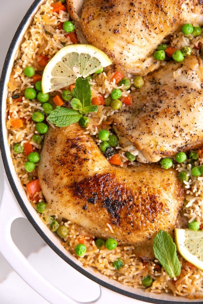 Large white skillet filled with arroz con pollo with peas and finely chopped red bell pepper and garnished with fresh mint and lemon slices.