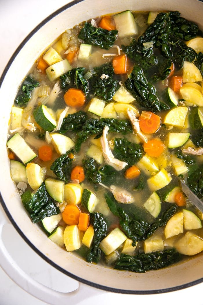 Large ceramic Dutch oven filled with homemade soup filled with shredded chicken, onions, carrots, celery, kale, zucchini, and yellow squash.