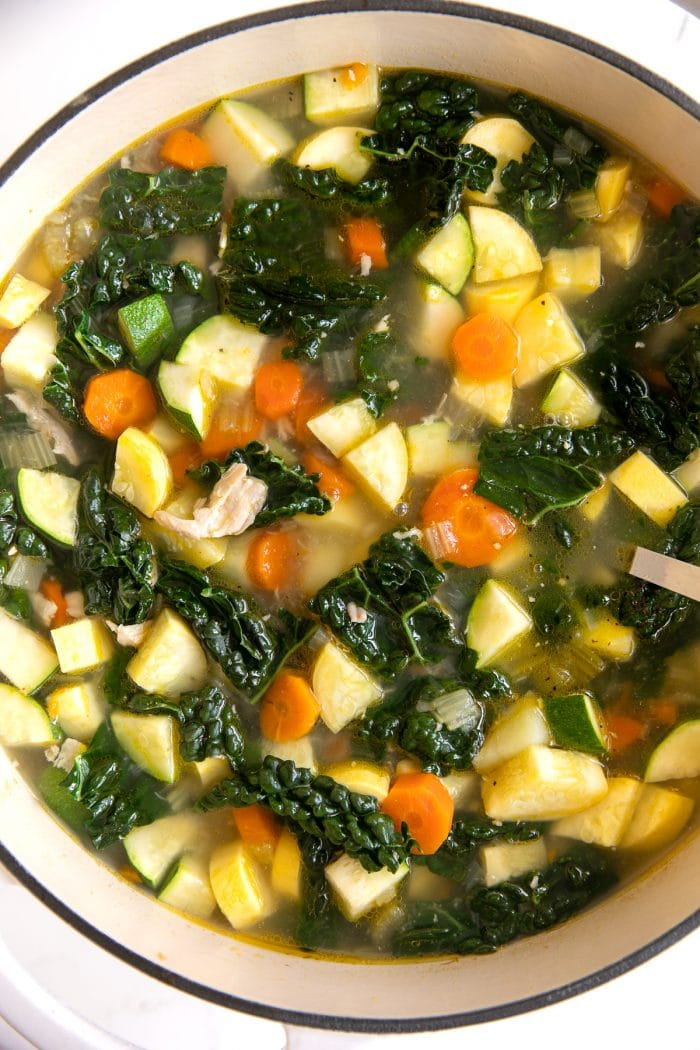 Overhead image of a large ceramic Dutch oven filled with homemade soup filled with shredded chicken, onions, carrots, celery, kale, zucchini, and yellow squash.