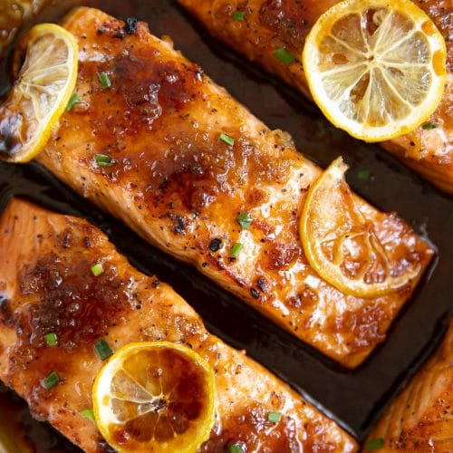 Close-up overhead image of four equal-sized cooked salmon covered in a homemade honey garlic sauce.