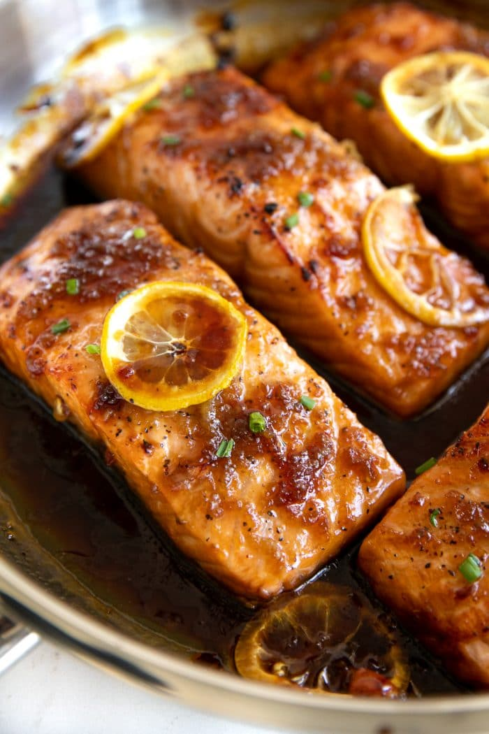 Close up image of honey garlic salmon fillets in a large stainless steel pan.