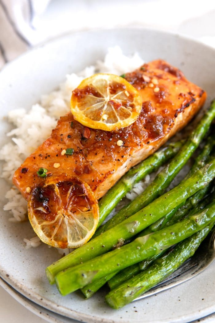 Medium sized dinner plate filed with white rice, cooked asparagus, and one salmon fillet covered in a honey garlic sauce.