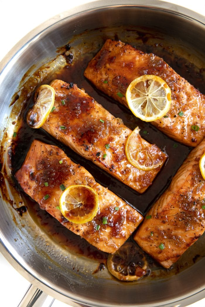 Large stainless steel skillet filled with four salmon fillets cooked in a homemade honey garlic sauce with fresh lemon slices.