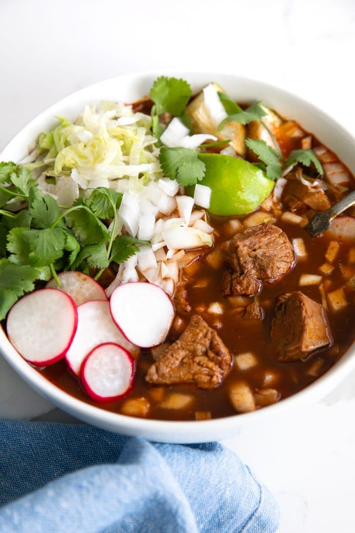 Image of a white bowl filled with posole rojo and topped with cabbage, lettuce, cilantro, and sliced radish.